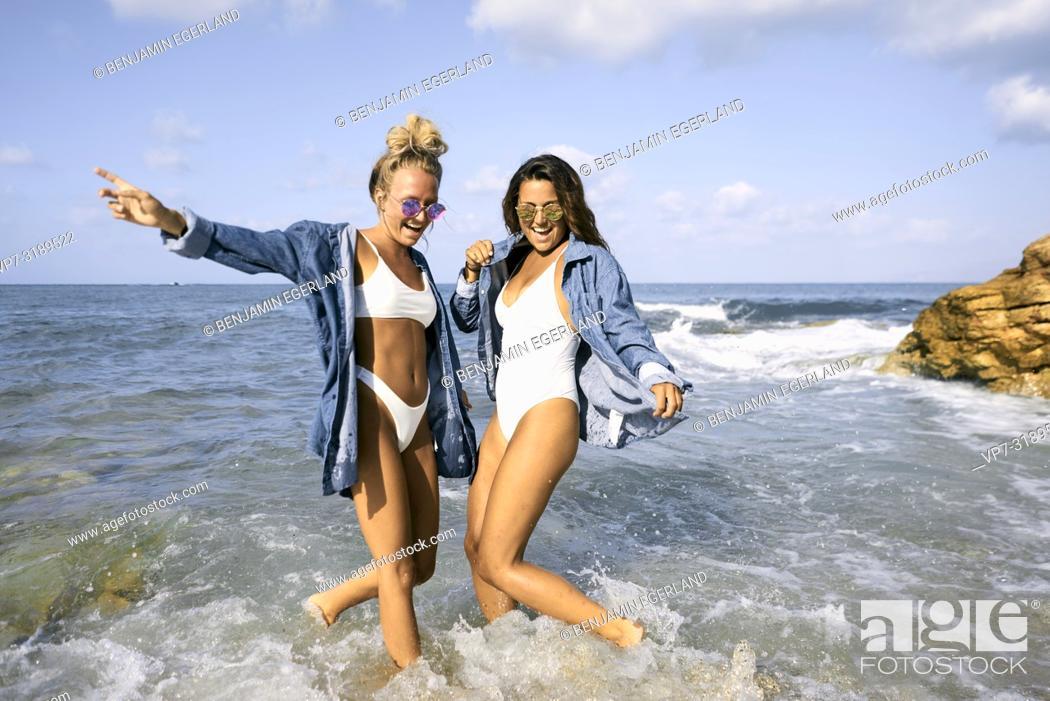Stock Photo: Two women jumping in sea water at beach, Chersonissos, Crete, Greece.