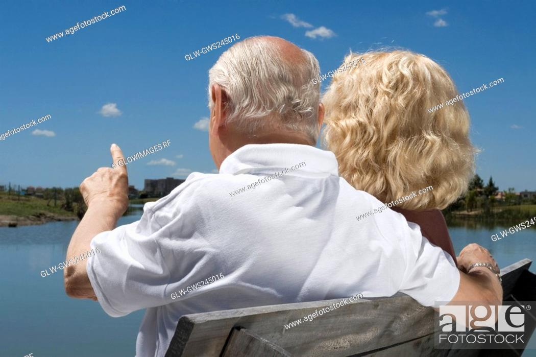 Stock Photo: Rear view of a senior couple sitting on a bench at the lakeside.