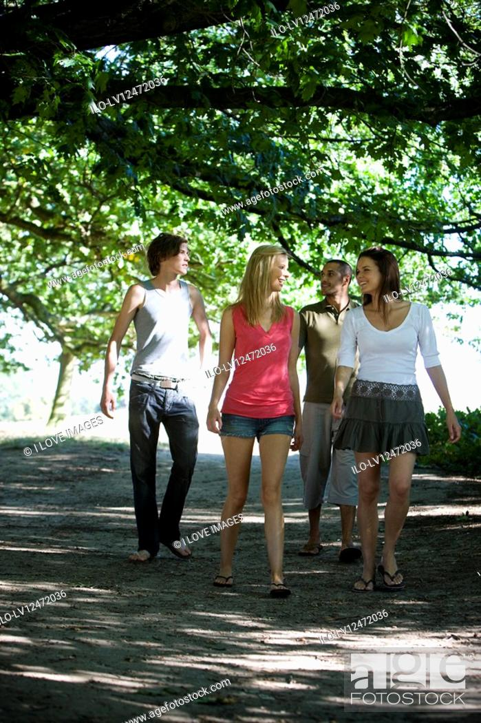 Stock Photo: Four friends walking along a path.