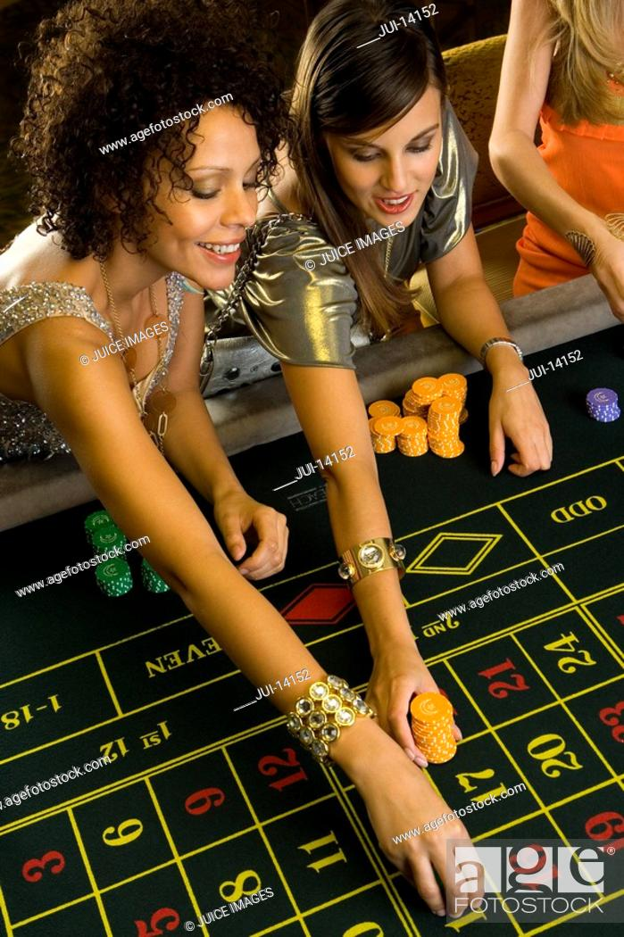 Stock Photo: Woman and friend placing gambling chips on roulette table, elevated view.