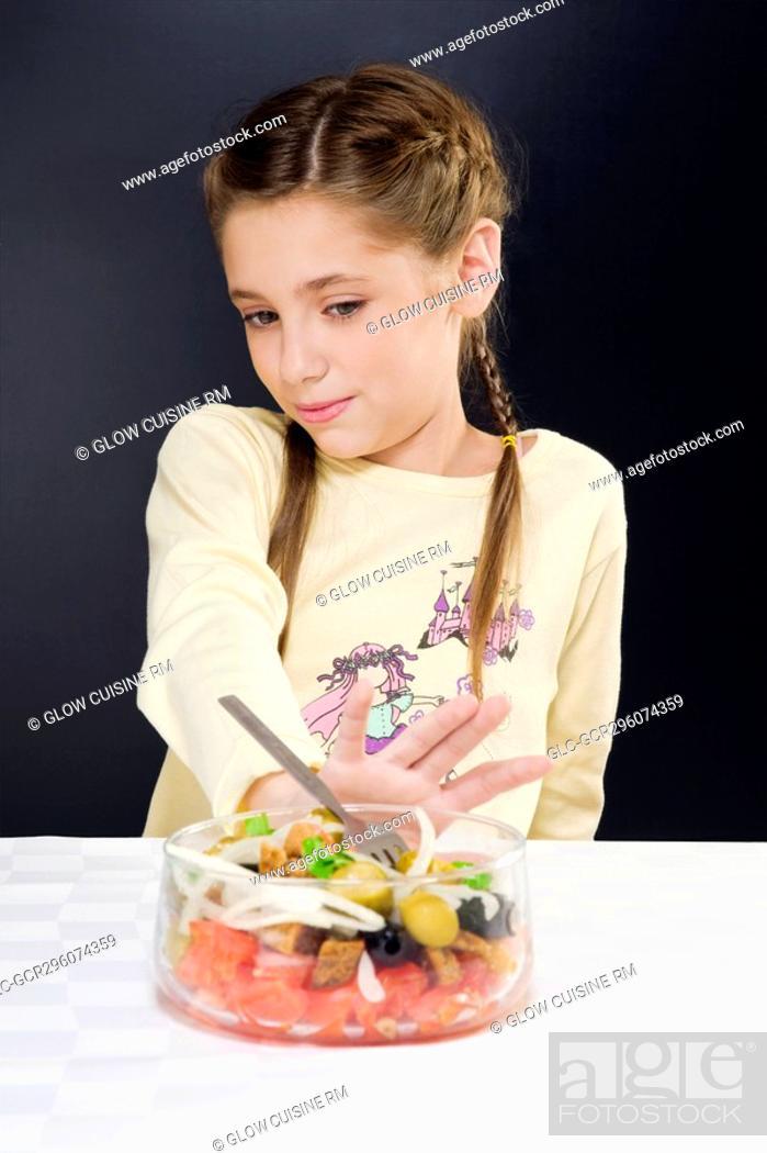 Stock Photo: Close-up of a girl pushing a bowl of salad away.