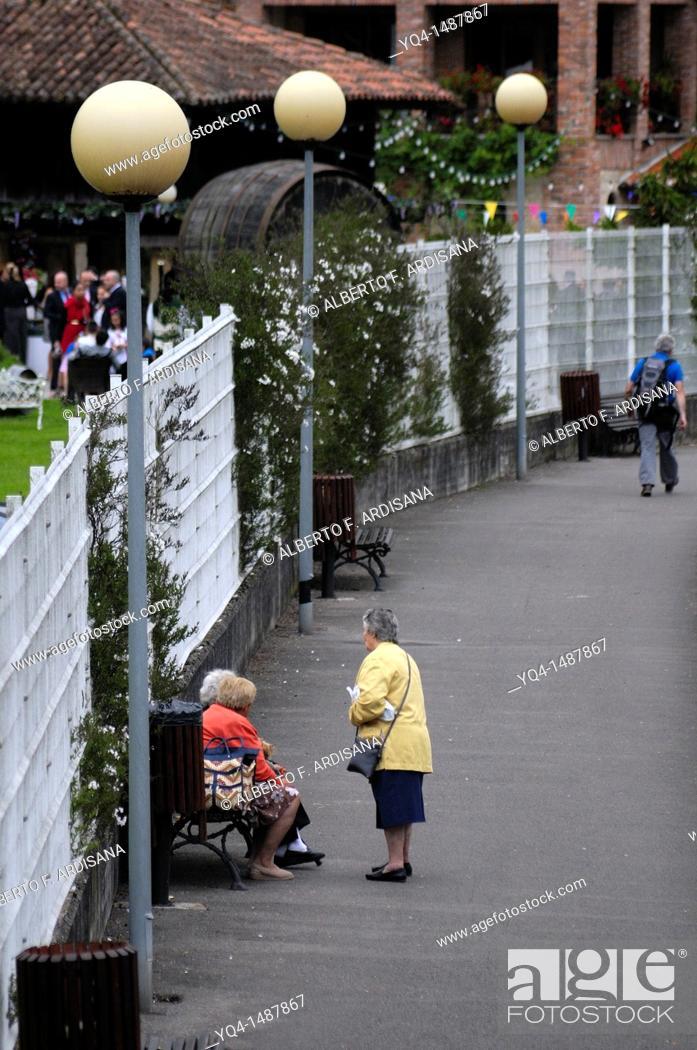 Stock Photo: Senior women conversing on a bench, Cangas de Onis, Asturias, Spain.