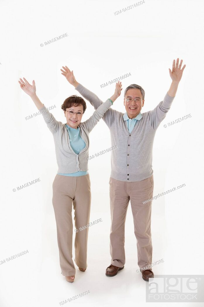 Imagen: Senior man and woman standing with arms outstretched.