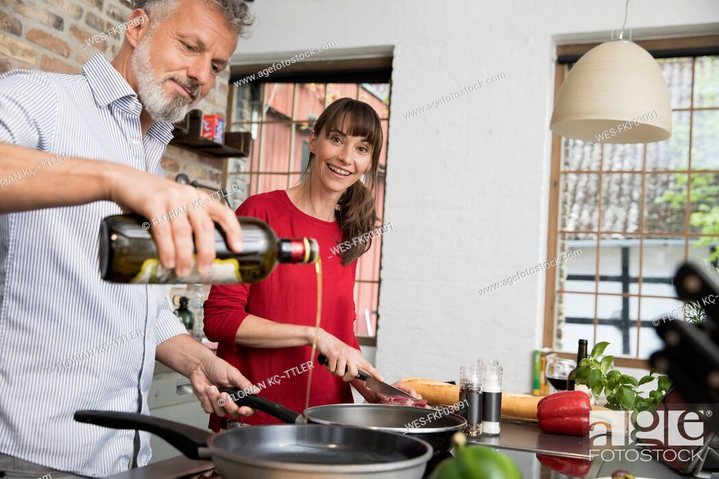 Stock Photo: Couple in kitchen, preparing food toghether.