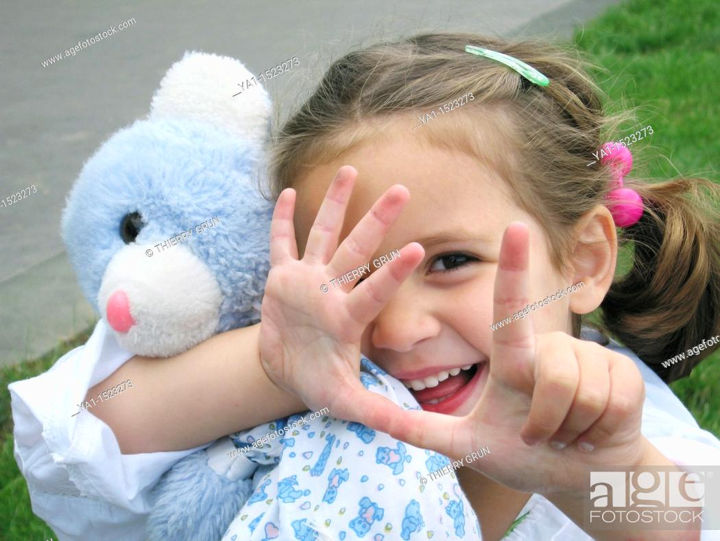 Stock Photo: Young girl hugging her teddy bear and counting with fingers.
