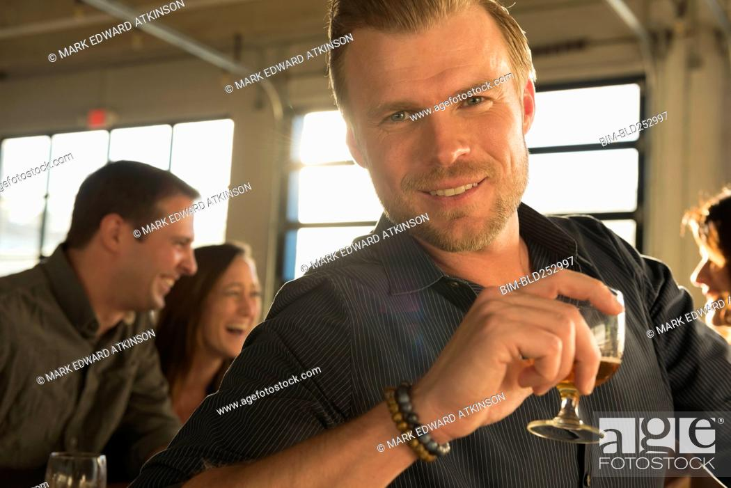Stock Photo: Portrait of smiling Caucasian man drinking beer with friends in brew pub.