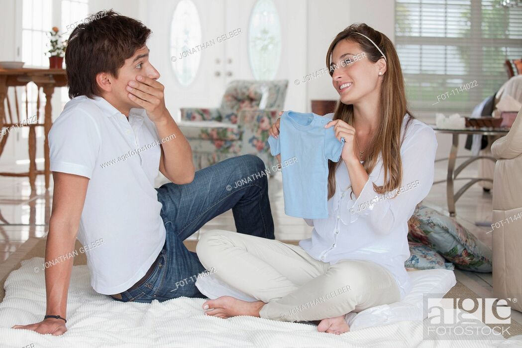 Stock Photo: A man looking shocked at the blue baby shirt his girlfriend is showing him.