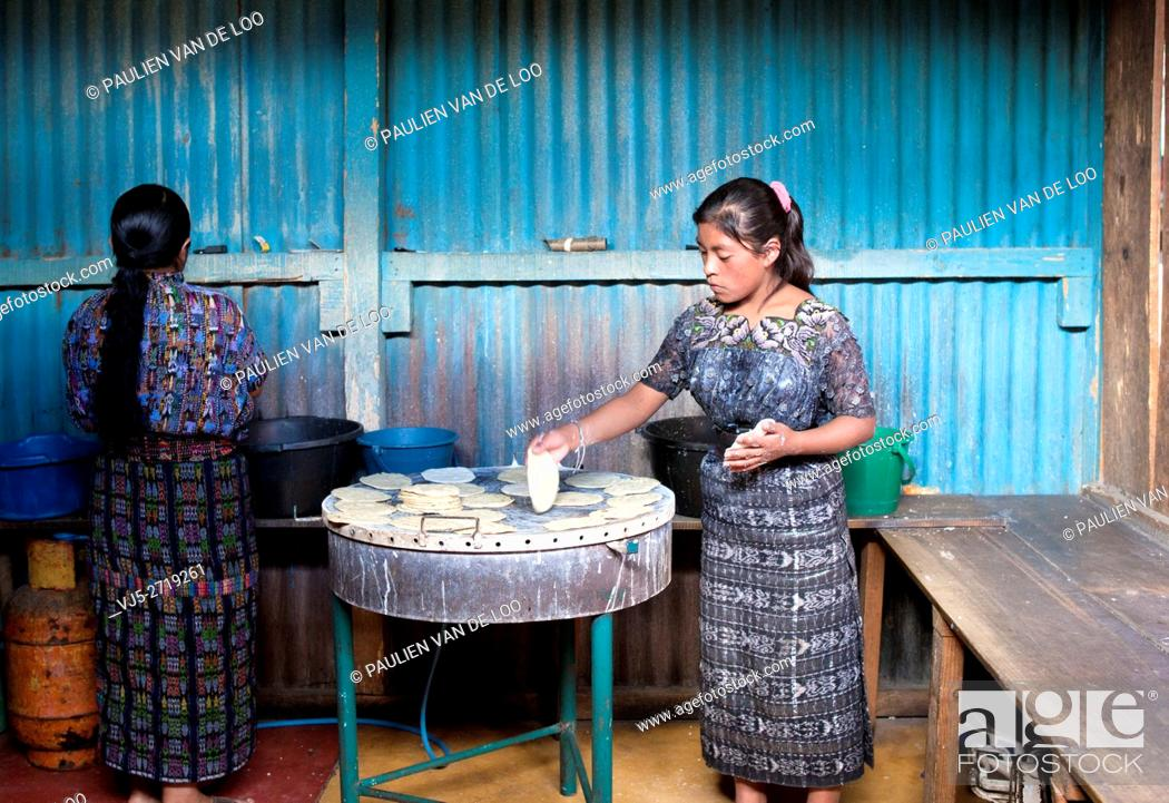 Stock Photo: Antigua, Guatemala. Women baking bread and pancakes for shopping and hungry customers walking by her shop inside an indoor market.