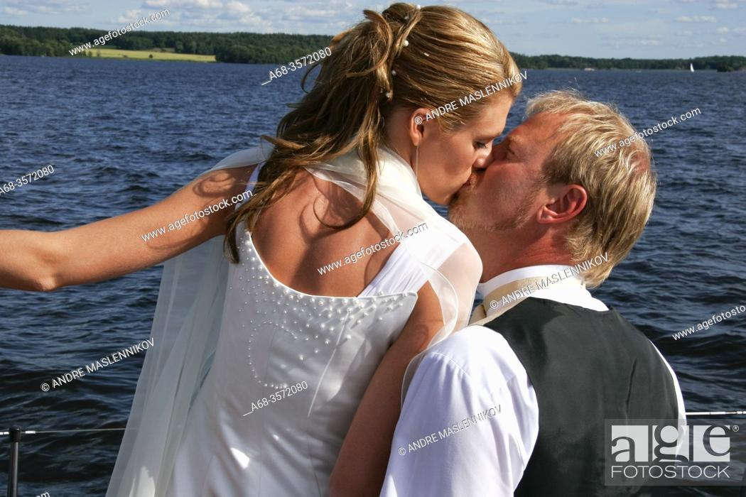 Stock Photo: Wedding. The bride and groom go by boat to the party. Model release. Photo: André Maslennikov.