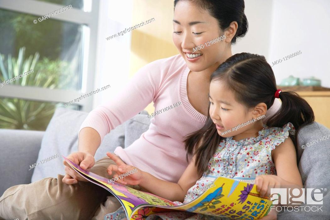 Stock Photo: Mother sitting with daughter on sofa reading a book.