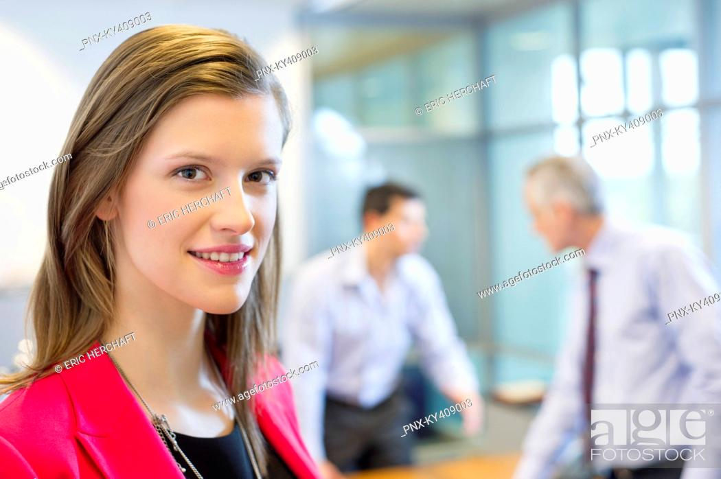 Stock Photo: Portrait of a businesswoman smiling in an office with her colleagues discussing in the background.