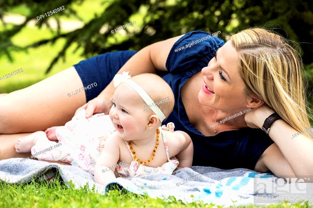 Photo de stock: A young mother playing with her baby on a blanket in a city park on a warm summer day; Edmonton, Alberta, Canada.
