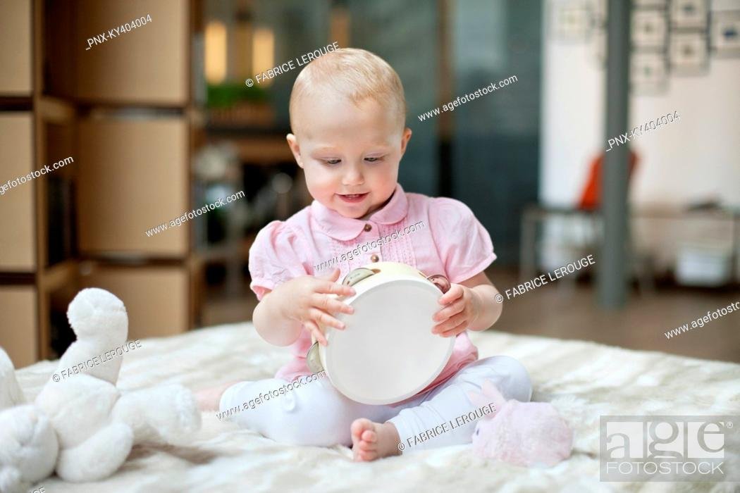 Stock Photo: Baby girl playing with a tambourine.