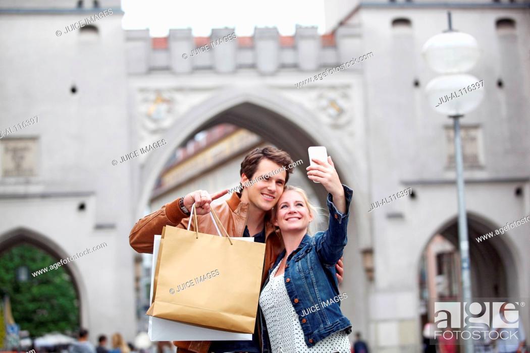 Imagen: Mid adult couple taking selfie in front of Neuhauser Tor, Munich, Bavaria, Germany, Europe.