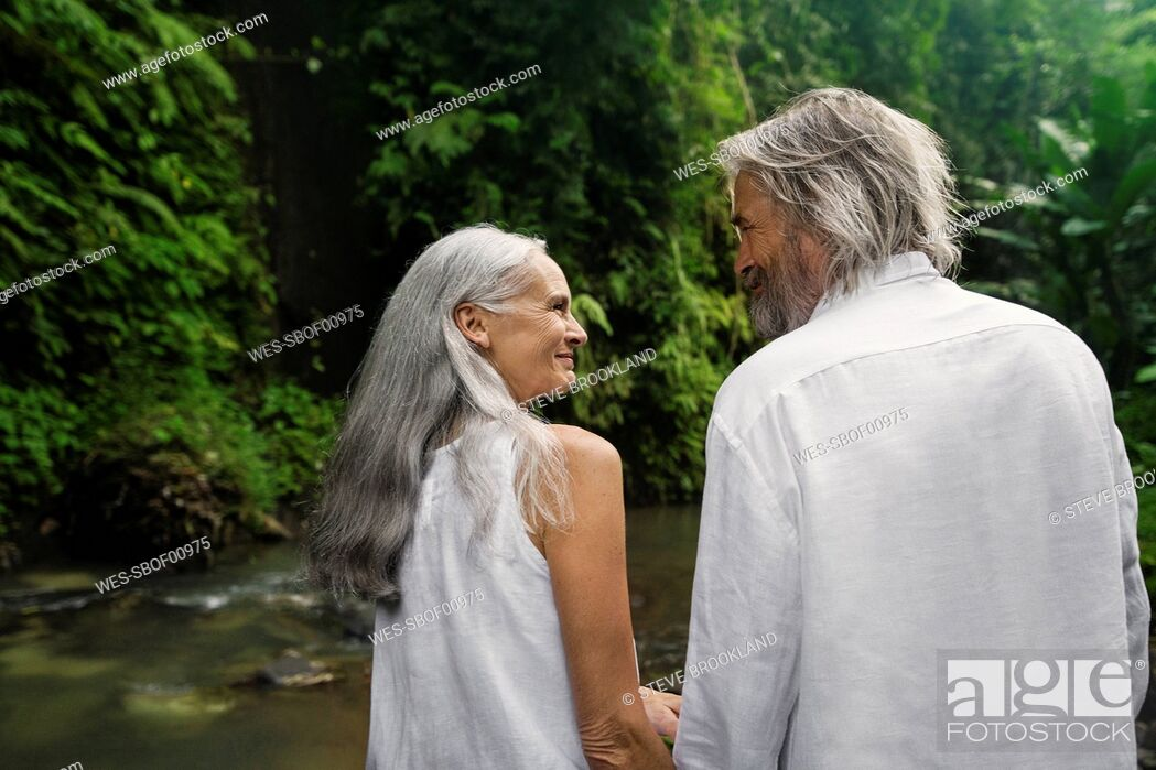 Stock Photo: Handsome senior couple smiling at each other in tropical jungle.