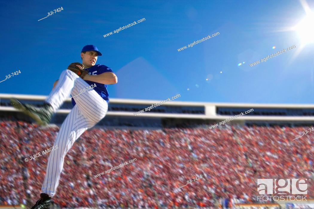 Stock Photo: Baseball pitcher, in blue uniform, preparing to throw ball during competitive game, side view lens flare, surface level.