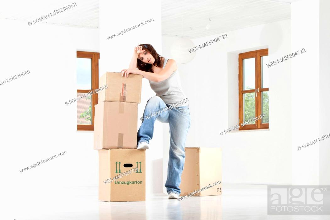 Stock Photo: Young woman leaning on cardboard boxes.