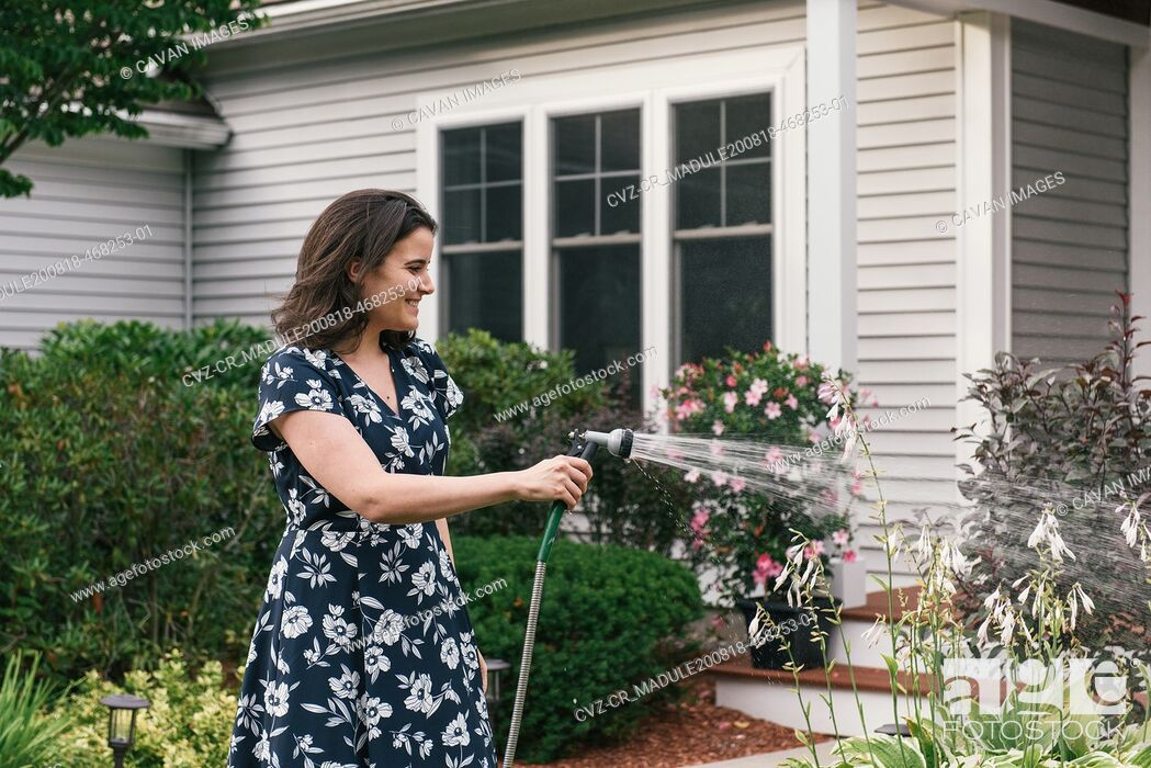 Imagen: Adult woman smiling while watering plants with hose in front of home.