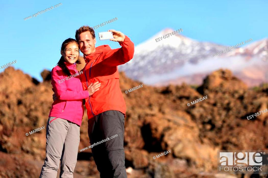 Imagen: Couple taking selfie hiking in beautiful nature with smart phone. Happy couple walking enjoying view and taking pictures with smartphone.
