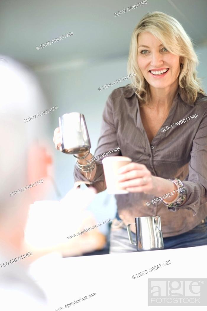Stock Photo: Woman serving coffee in food cart.