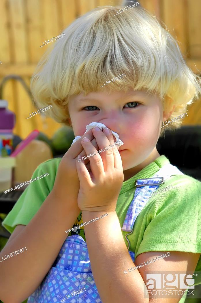Stock Photo: 4 year old girl with allergies cleans nose with tissue.