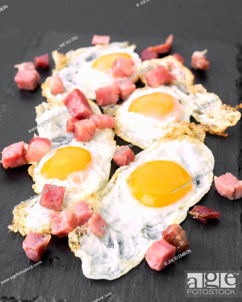 Photo de stock: fried quail egg with baked ham on black stone.