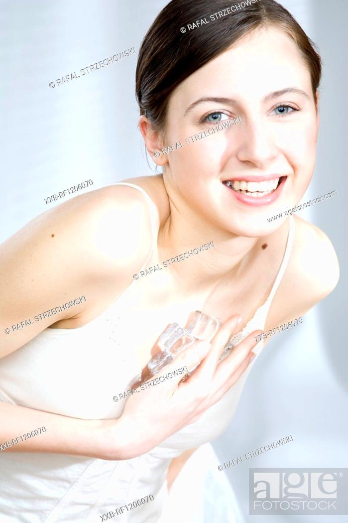 Stock Photo: woman putting ice cubes on neckline.