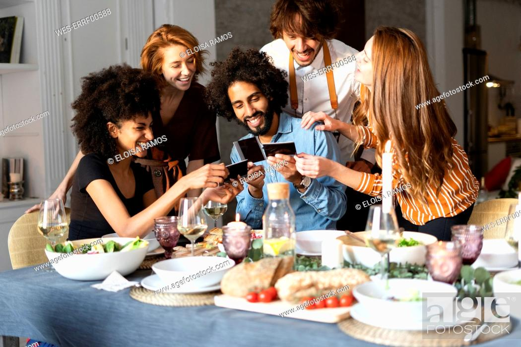 Stock Photo: Friends sitting at dining table, looking at photographs.