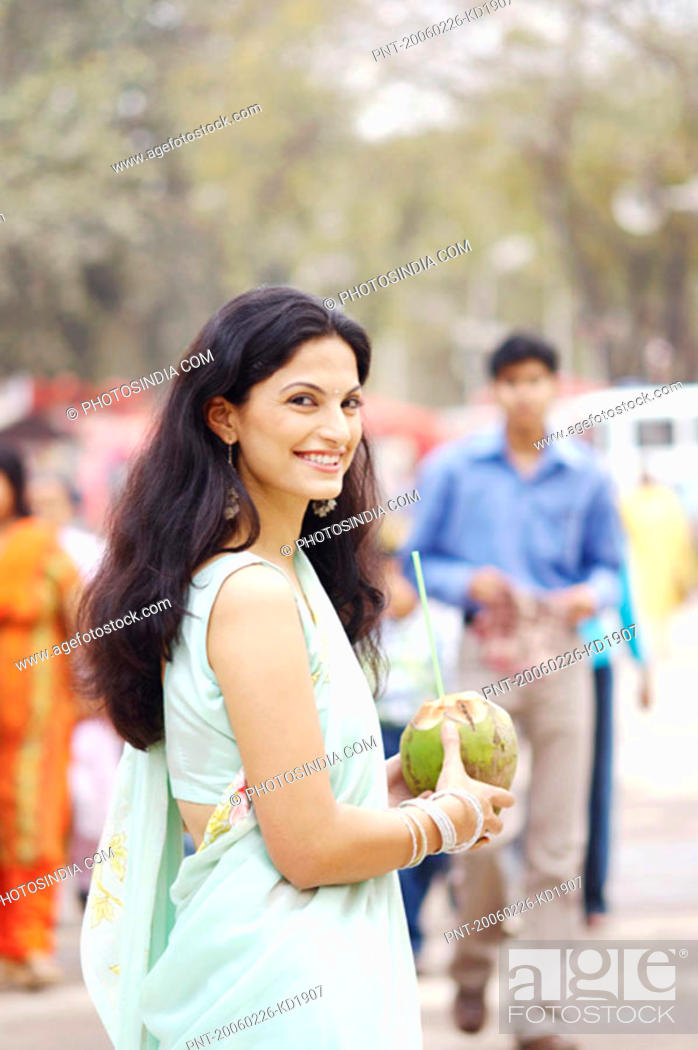 Stock Photo: Portrait of a young woman holding a coconut smiling.