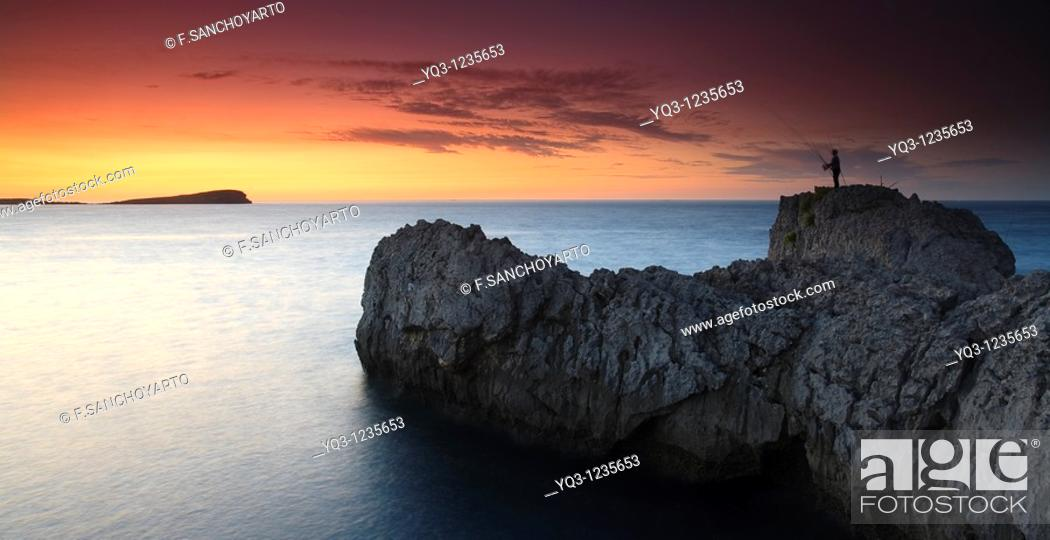 Stock Photo: Fisherman at sunset on the Punta del Najo, Islares, Castro Urdiales, Cantabria, Spain.