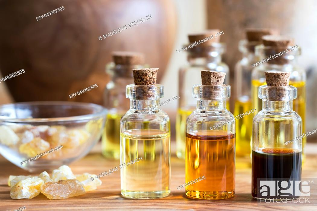 Stock Photo: Bottles of essential oil with rankincense resin on a wooden table.