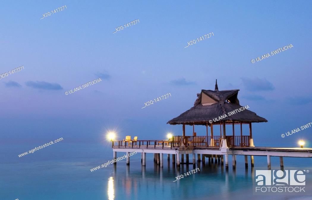 Stock Photo: Gazebo and jetty with straw roof at a resort in the Maldives at dusk.