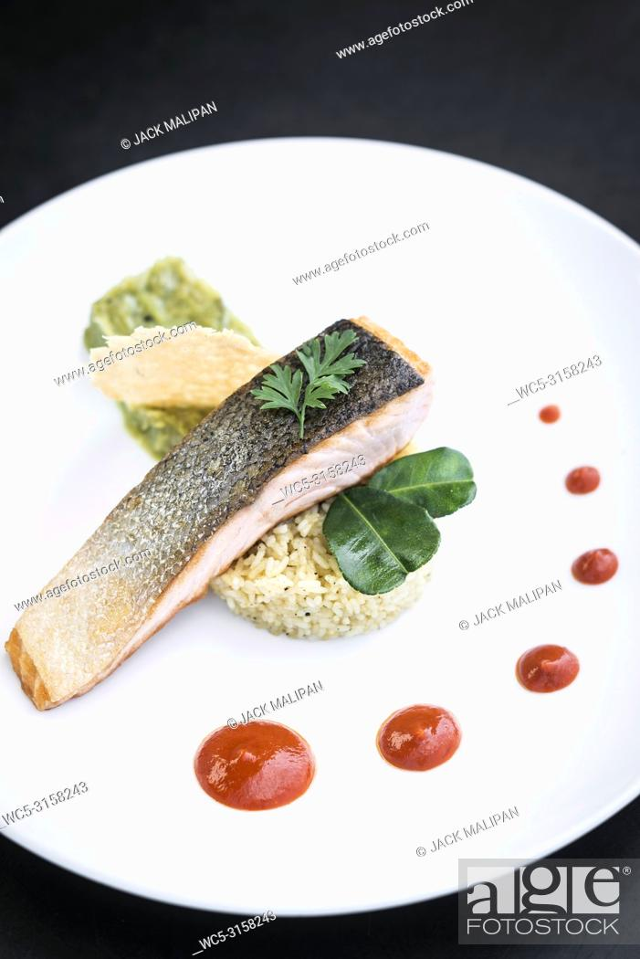 Photo de stock: gourmet salmon fish fillet with rice guacamole and red pepper sauce meal.