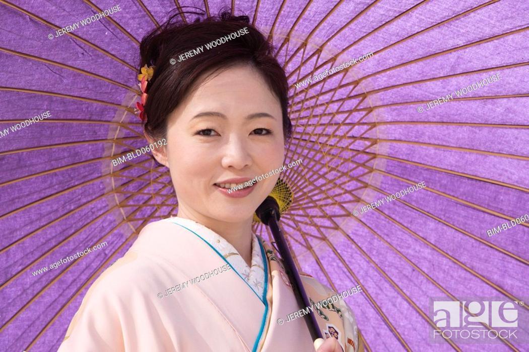 Stock Photo: Asian woman holding parasol.