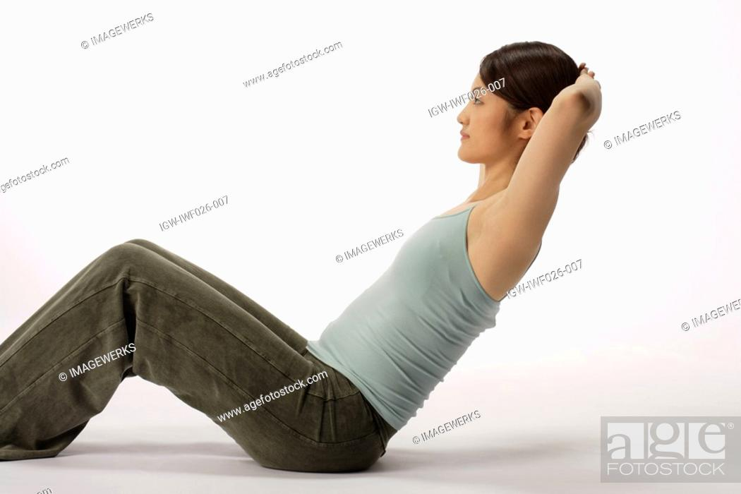 Stock Photo: View of a young woman doing sit-up.