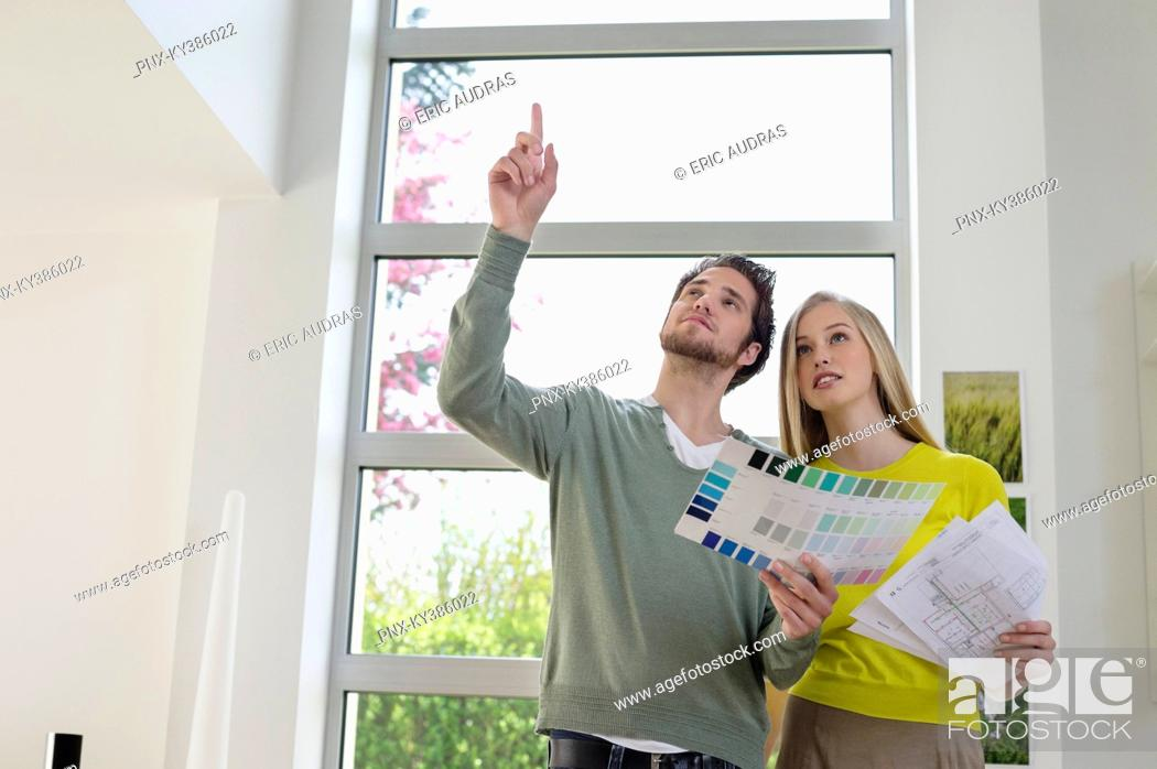 Stock Photo: Couple choosing color for their house from a color chart.