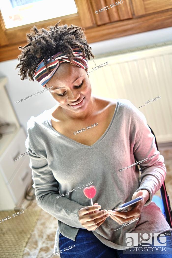 Imagen: Closeup retrato de una joven negra con peinado afro bromeando con un teléfono móvil y una paleta de interior en casa. Concepto de estilo de vida.