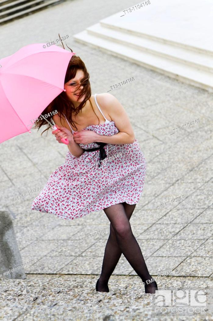 Stock Photo: Attractive young woman is surprised by the very strong wind.