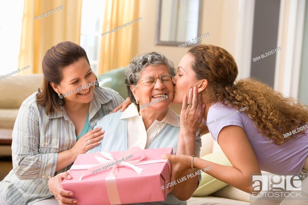 Stock Photo: Hispanic woman giving gift to grandmother.
