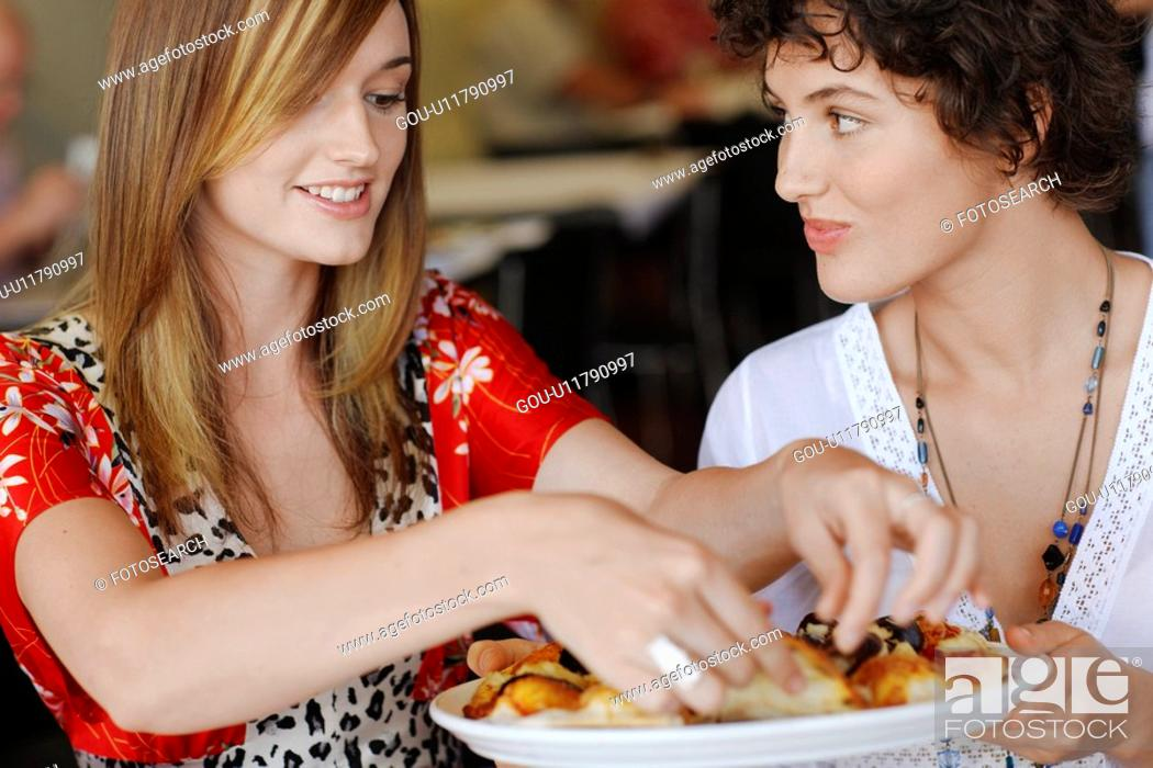 Stock Photo: Young women eating pizza.