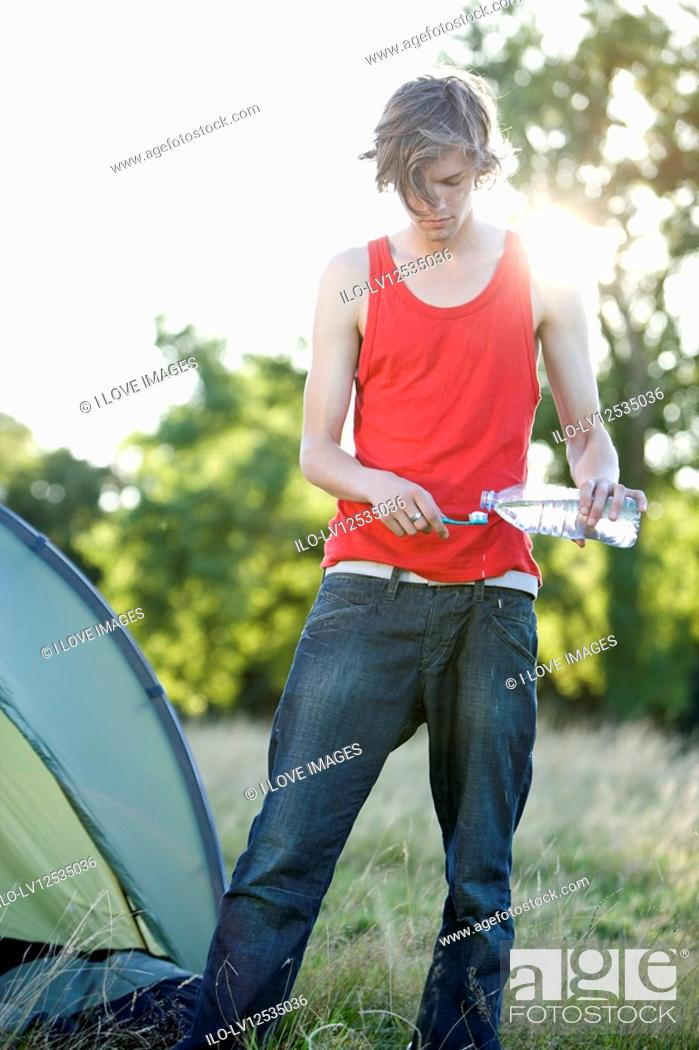 Stock Photo: A young man camping, pouring water on his toothbrush.