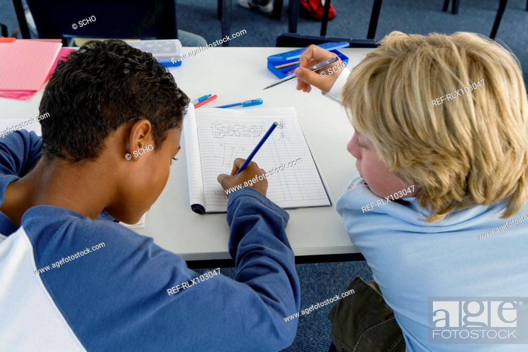 Stock Photo: Two boys 10-13 in classroom working together over exercise, team work.