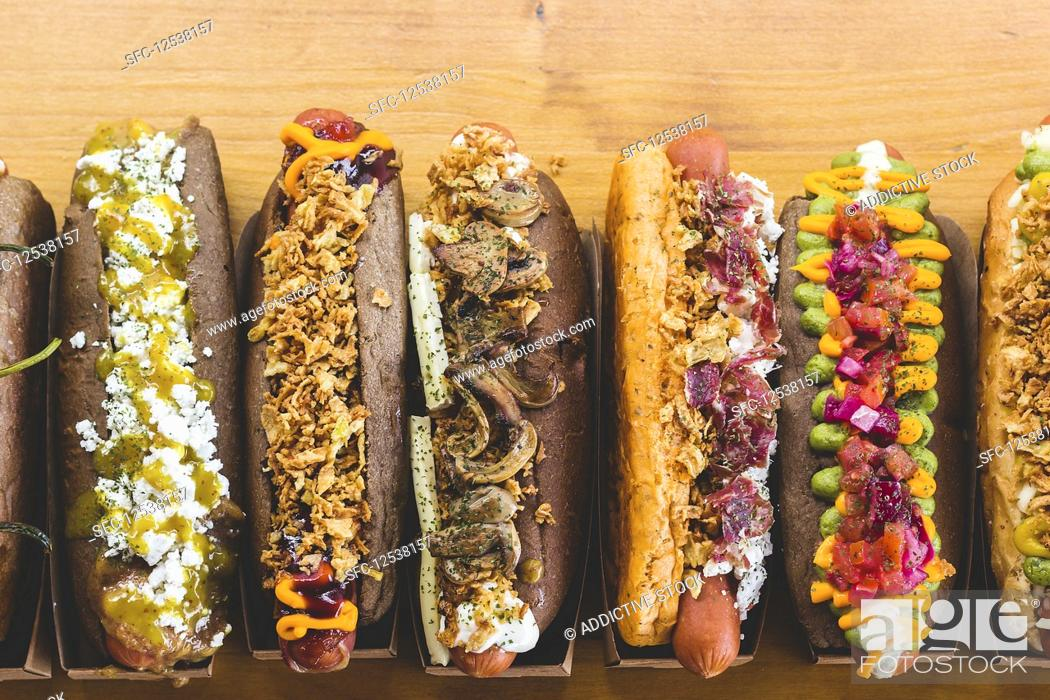 Stock Photo: Row of assorted hot dogs with different delicious toppings and fillings.