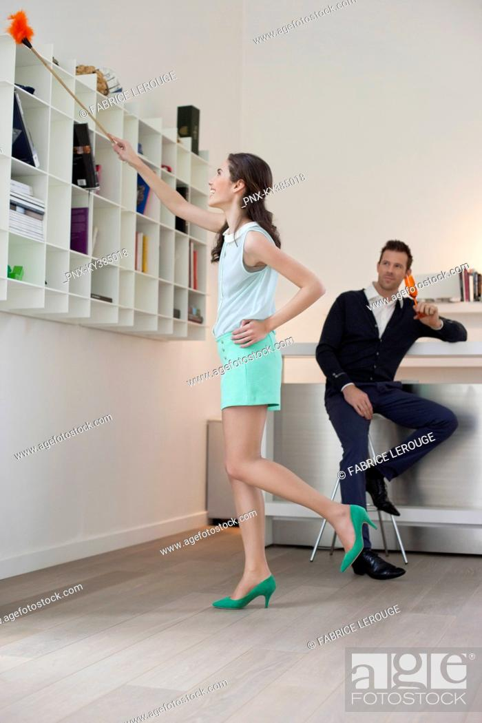 Stock Photo: Woman cleaning a bookshelf and her husband drinking champagne in the background.