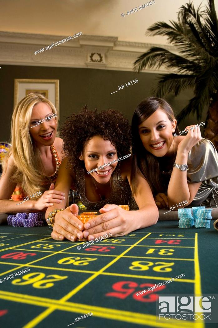 Stock Photo: Young woman collecting pile of gambling chips from roulette table, flanked by friends, smiling, portrait.