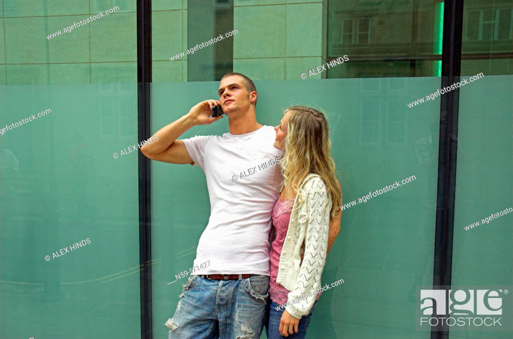 Stock Photo: Attractive young urban couple, man talking on mobile phone.
