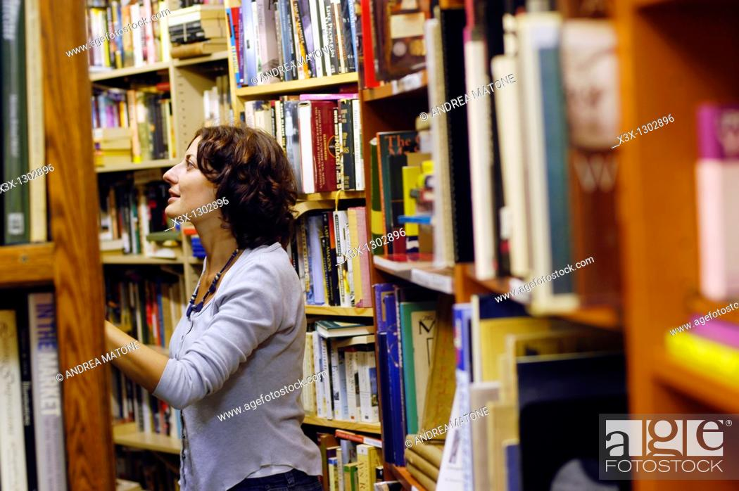 Stock Photo: Woman enthusiastically admiring books in a book store.