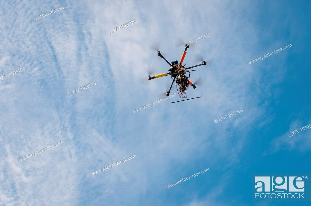 Stock Photo: A drone with a camera hovers overhead in the sky.