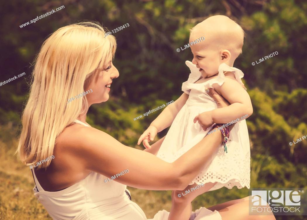 Photo de stock: A vintage style image of a beautiful young mother with long blonde hair enjoying quality time with her cute baby daughter sitting on the grass in a city park on.