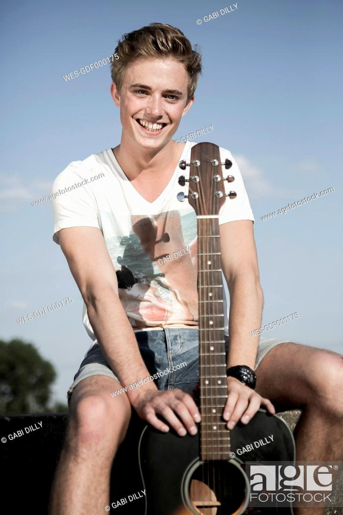 Imagen: Germany, Young man sitting in park, holding guitar.